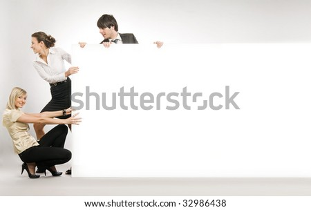 Business people pulling big white board, lots of copyspace - stock photo