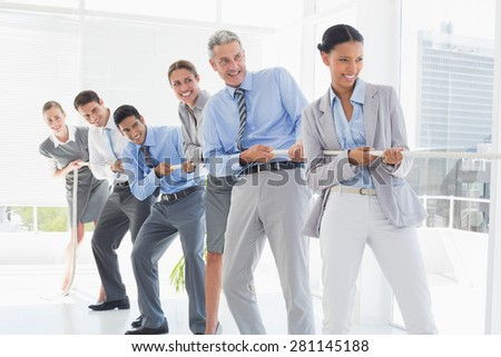 Business people pulling rope in office - stock photo