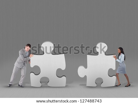 Business people pushing two jigsaw pieces together on grey background