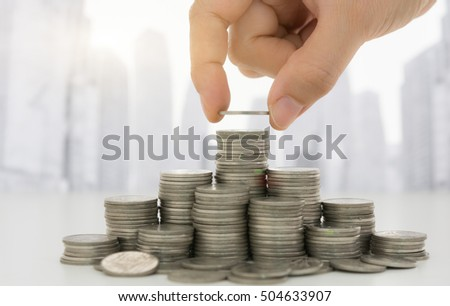 Business people putting coin on stack of money with city background. Concepts of finance, investing, investment, savings, finance planning,