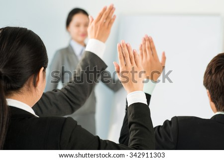 Business people raising hands to answer in training