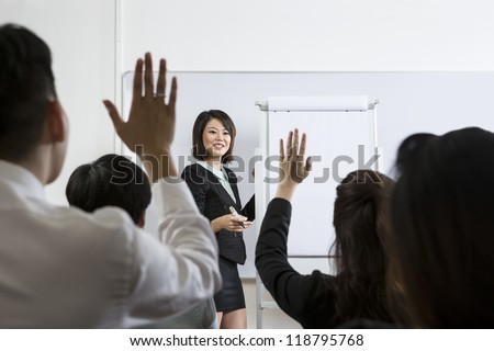 Business people Raising there Hand Up at a Conference to answer a question - stock photo