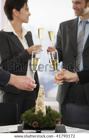 Business people raising toast over meeting table with Christmas decoration at office. Focus placed on flutes in front.