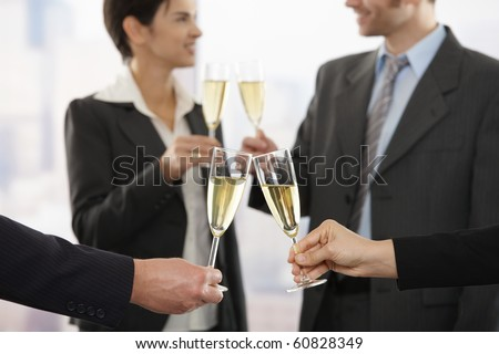 Business people raising toast with champagne at office, focus placed on flutes. - stock photo