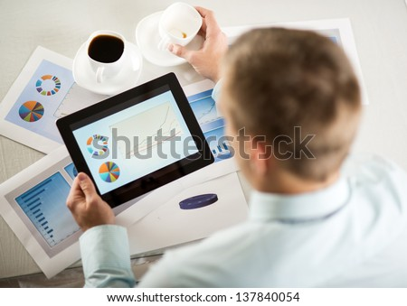 Business people reading business graphs and charts - stock photo