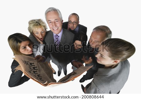 Business people reading newspaper against white background elevated view - stock photo