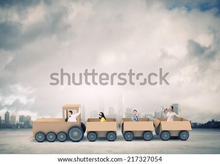 Business people riding carton train. Teamwork concept - stock photo