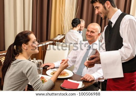 Business people served by waiter enjoy lunch at the restaurant