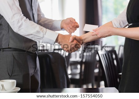 Business people shaking hands after meeting and changing cards in restaurant - stock photo