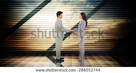Business people shaking hands against room with large window looking on landscape - stock photo