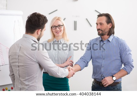 Business people shaking hands and finishing up meeting. Communication between two companies or firms in office. - stock photo