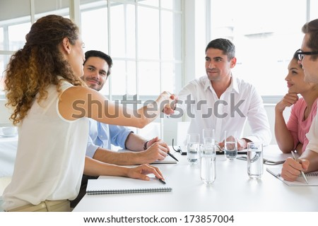 Business people shaking hands at conference table in office - stock photo
