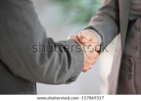 Business people shaking hands close up in an office