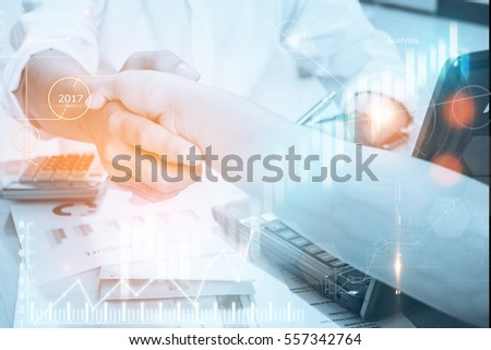 Business people shaking hands, finishing up a meeting,blue digital diagram finance chart and graph,color filters