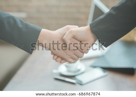 Business people shaking hands, finishing up a meeting, shaking hands success deal, Young businesswoman going to make handshake with a businessman -greeting, dealing, merger and acquisition concepts