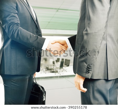 Business people shaking hands in an office. - stock photo