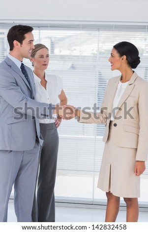 Business people shaking hands in bright office while colleague watching them