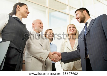 Business people shaking hands in front of a modern office centre - stock photo