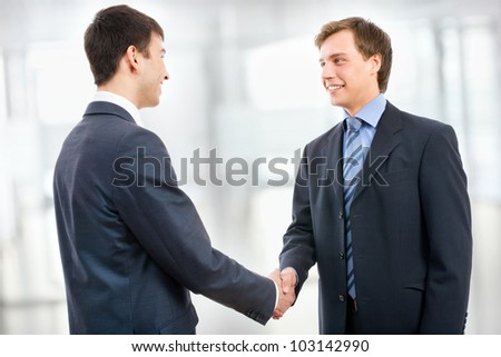 Business people shaking hands in modern office - stock photo