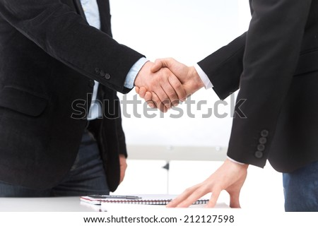 Business people shaking hands in office. businessman shaking hands to seal deal with his partner  - stock photo