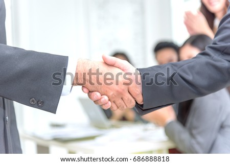 Business people shaking hands in the office with business team blurr background,success concept,selective focus,copy space.