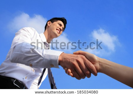 business people shaking hands on blue sky background - stock photo