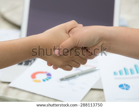 Business people shaking hands over business document - stock photo