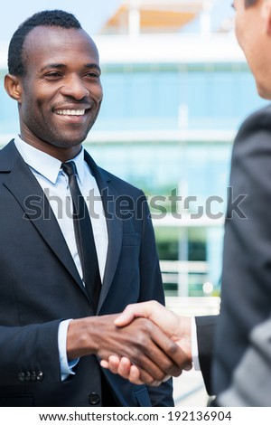 Business people shaking hands. Two business men shaking hands and smiling while standing outdoors - stock photo