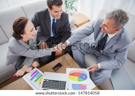 Business people shaking hands while working in cosy meeting room