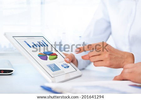 Business people show touchpad tablet with financial graph, businesswoman report point finger using touch screen at office desk - stock photo