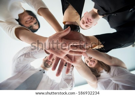 Business people showing unity by stacking hands together - stock photo