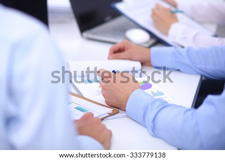 Business people sitting and writting at business meeting, in office - stock photo
