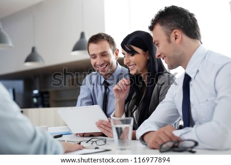 Business people sitting at the desk working with digital tablet - stock photo