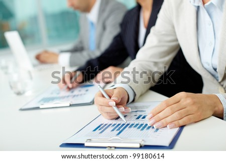 Business people sitting at the table and analyzing graphs - stock photo