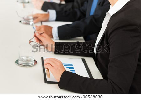 Business - people sitting in a meeting, close-up on hands and woman in the front - stock photo