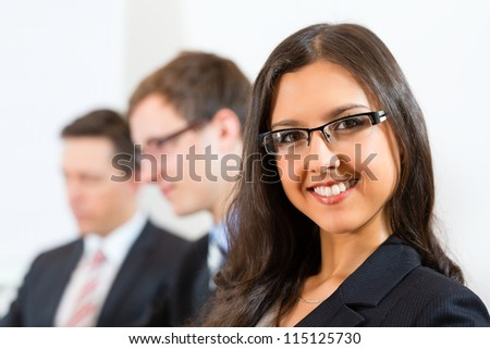 Business people sitting in a meeting or workshop in an office, one woman is looking into the camera - stock photo