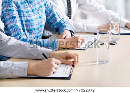 Business people sitting in a row and writing notes. Close-up of writing hands. - stock photo