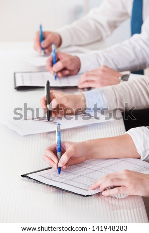 Business People Sitting In A Row And Writing Notes In Office