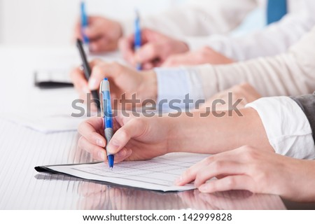 Business People Sitting In A Row And Writing Notes In Office - stock photo