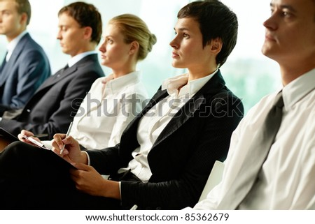 Business people sitting in a row at seminar