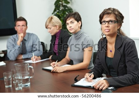 Business people sitting in a row on business training, listening and writing notes. - stock photo