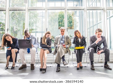 Business people sitting in a waiting room during company's bankruptcy - Depressed team of businessmen waiting for a job interview - Concepts about business, bankruptcy, crisis and economic depression - stock photo