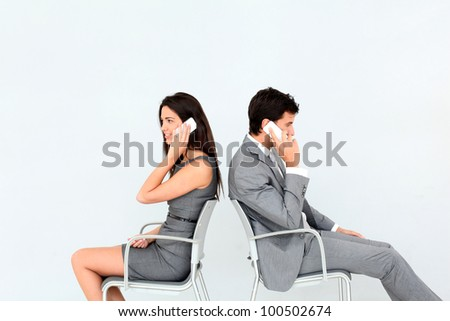 Business people sitting in chairs with mobile phone - stock photo
