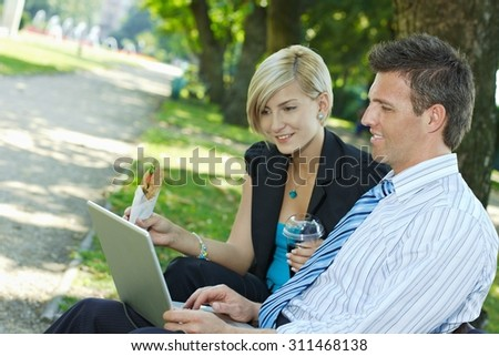 Business people sitting in park with laptop while having breakfast, outdoor. Smiling, happy, looking at screen.