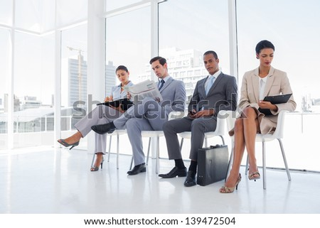 Business people sitting in waiting room with big windows - stock photo