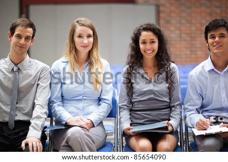 Business people sitting on chairs during a presentation - stock photo