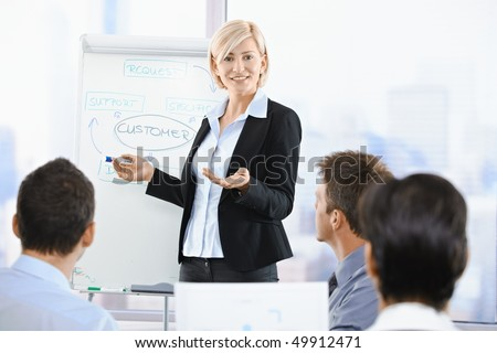Business people sitting on presentation at office. Businesswoman presenting on whiteboard. - stock photo