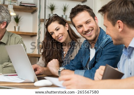 Business people smiling together while sitting at desk in office  - stock photo