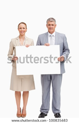 Business people smiling while holding a poster against white background