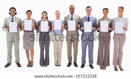 Business people smiling while holding white support for letters against white background - stock photo